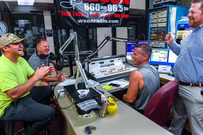 "The ""Living Outdoors"" crew. left to right, Justin Cessna, Joey Thomas and Logan Tompkins share a laugh with sports director Greg Busby before taping an episode of their show at the WSON studio in the City Center Building Wednesday, August 26, 2020."