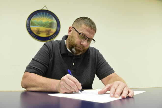 Former Crestline police Chief Joe Butler signs final paperwork Thursday afternoon inside the law office of Attorney Roberta Wade in Galion.