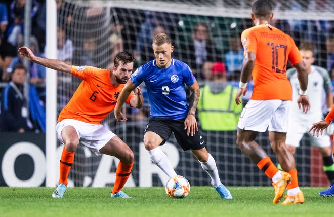 Estonia's Erik Sorga, center, fights for the ball with Netherlands' Davy Propper, left, during the Euro 2020 group C qualifying soccer match between Estonia and Netherlands at the A. Le Coq Arena in Tallinn, Estonia, Monday, Sept. 9, 2019. (AP Photo/Raul Mee)