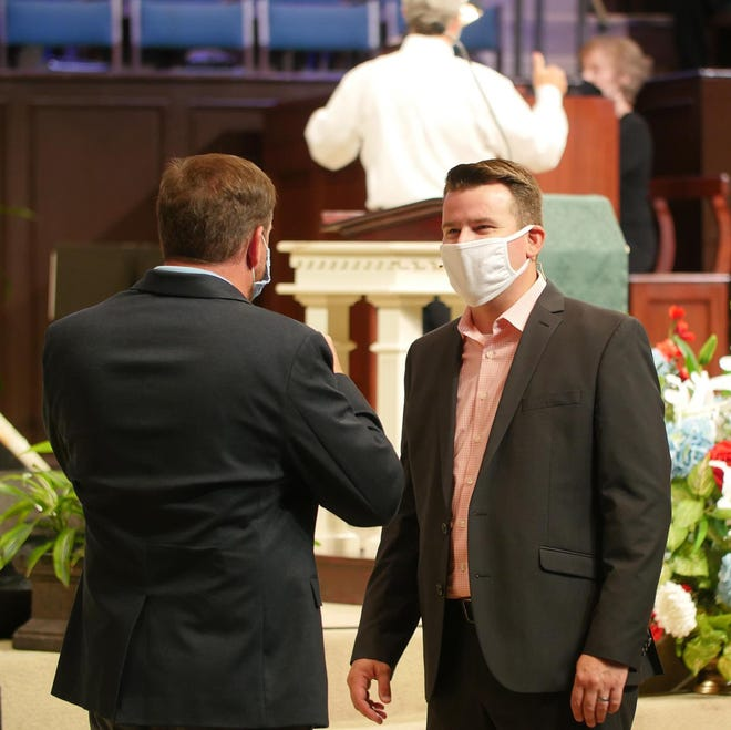 Dr. Chris Montgomery (right), senior pastor at Frazer United Methodist Church, speaks to a musician before a recently televised worship service.