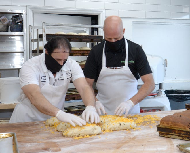 Wearing masks and kneading loaves of Jalapeno cheddar bread at Aspen Mills Bakery and Café in Palm Springs are baker Julio Limones, left, and Marty Webster, owner of the business.