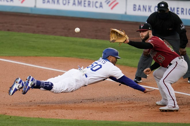 Los Angeles Dodgers' Mookie Betts, left, dives back to first base on a pickoff attempt, next to Arizona Diamondbacks first baseman Christian Walker during the first inning of a baseball game Wednesday, Sept. 2, 2020, in Los Angeles. (AP Photo/Marcio Jose Sanchez)