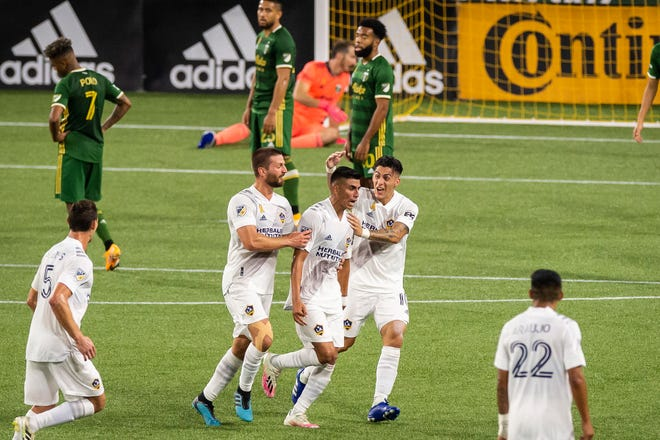 Los Angeles Galaxy midfielder Joe Corona (15) celebrates with teammates midfielder Perry Kitchen (2) and forward Cristian Pavon (10) after scoring a goal in the second half at Providence Park. The Los Angeles Galaxy won 3-2.