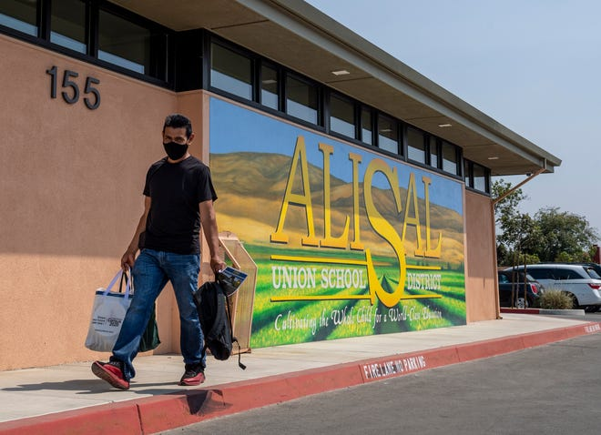A father carries a backpack, school supplies, and home goods as he walks in front of the Alisal Union School District office during the Migrant Education Program Region XVI giveaway in east Salinas, Calif., on Wednesday, Sep. 2, 2020.
