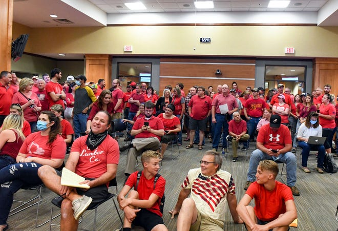 Over 200 people wear red in solidarity against a potential city-wide mask mandate during a city council meeting on Wednesday, September 2, in Brookings.