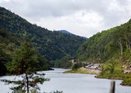 Cars zip by Lower Cascade Lake on State Route 73 on Saturday, Aug. 29, 2020. Cascade Mountain, for which the trailhead is located just down the road, often overflows with cars and might see 500-700 hikers on a single weekend day.