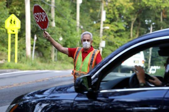 Crossing guard Joe Benke directs traffic near Douglas Grafflin Elementary School on the first day of school in Chappaqua Sept. 3, 2020.