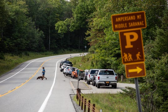 Hikers cross State Route 3 to access the Ampersand Mountain trailhead near Saranac Lake. They had to park on the side of the road since the lot with designated parking spots was already overflowing when they arrived on Monday, Aug. 31, 2020.