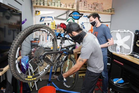 Luke Tancredi, owner of Crank Cycles on North Central Avenue in Hartsdale, works on a bike as employee Connor Eichinger looks on, Sept. 3, 2020.