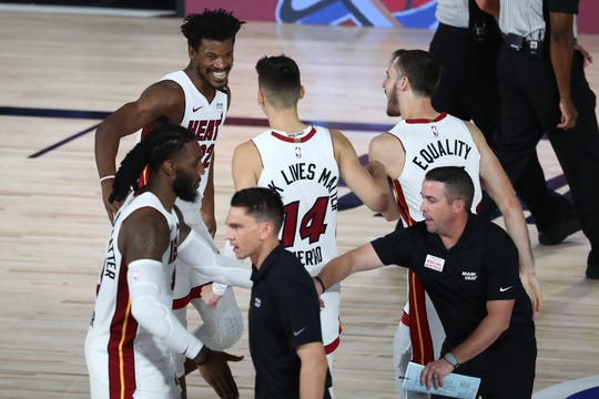 Jimmy Butler celebrates with teammates after hitting the free throws that gave the Heat the Game 2 victory over the Bucks.