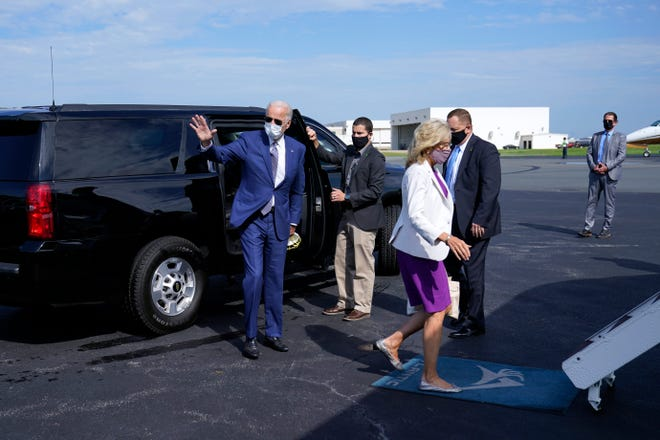Democratic presidential nominee Joe Biden, left, and his wife Jill walk to board a plane at New Castle Airport, in New Castle, Del., on Sept. 3, 2020, en route to Kenosha, Wis.