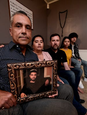 Rodrigo Arreola holds a photo of his slain son Hector Arreola, and sits with, from left, his daughter Patricia Arreola Ragan, her husband Jeff Ragan and their children Nadia and Ethan in Columbus, Ga., on Thursday September 2, 2020.