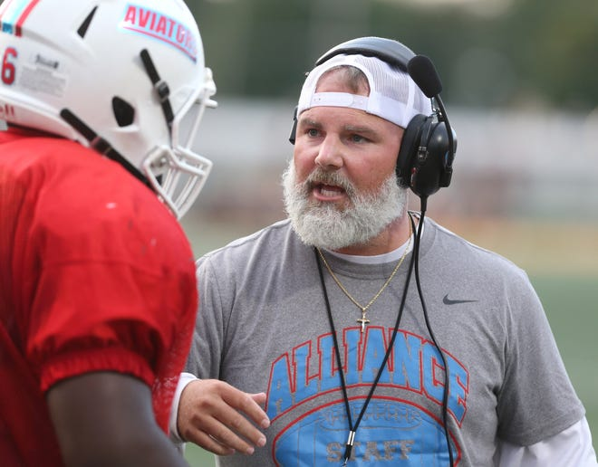 Alliance head coach Seth Whiting speaks with a player during their scrimmage at Hoover in August 2019.
