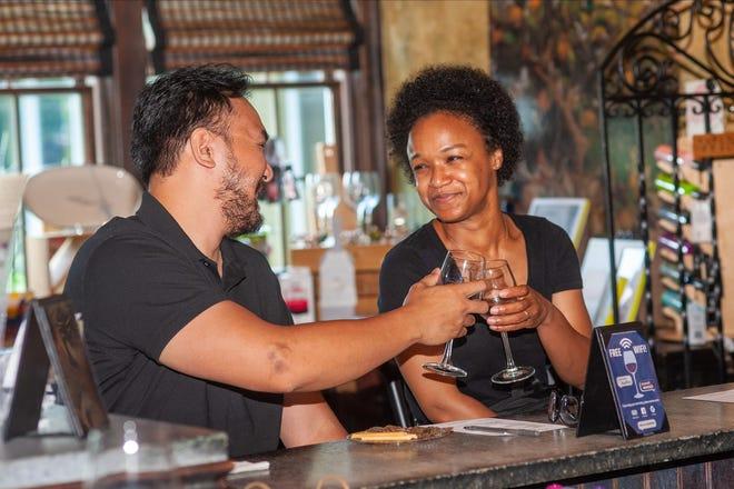 File - Kristian Delrosario and his wife Joanie Scott of Belleville taste wine in the tasting room at Crossing Vineyards in Upper Makefield in July.