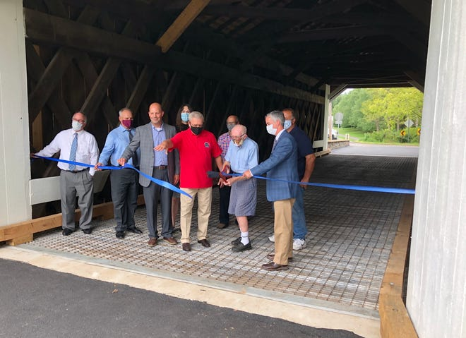 County officials open the Pine Valley Covered Bridge in New Britain Borough Thursday. The bridge is the last of seven county-owned covered bridges to receive repairs.