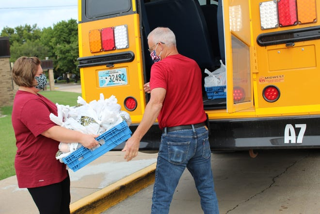 BPS child nutrition staff load up hundreds of meals on school buses outside Richard Kane Elementary for delivery to students at home.