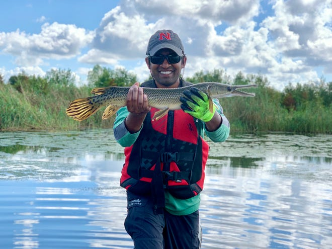 Assistant Professor of Biological Sciences Dr. Solomon David holds up a gar fish. David and the Gar Lab at Nicholls will share in a federal grant to improve the ecosystem of the Mississippi River.