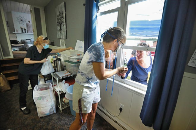 Volunteer Suzette Viola serves coffee to Shena Snodgrass through the window at the Helping Other People Excel. Benind Viola is volunteer Cindy Denney. The resource center offers food, clothing, personal items, and access to rehabilition to people from their 2594 Sullivant Ave. location. With COVID-19 restrictions, the staff has begun using a walk-up window service instead of having people come in the building. Staffers say the system has worked out well.  Photographed August 17, 2020. (Doral Chenoweth/Columbus Dispatch)