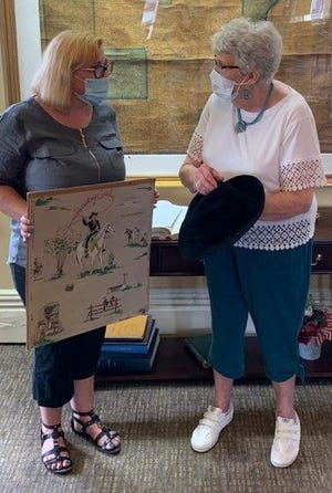 Shown discussing some of the Hopalong Cassidy memorabilia donated to the Belmont County Heritage Museum are curator Cathryn Stanley, left, and Laura Bates, who operated the Hopalong Cassidy Museum in Cambridge and organized the long-running Hopalong Cassidy Festival.