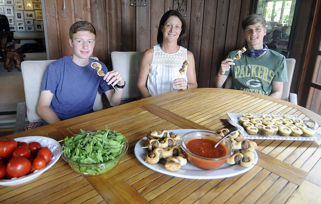 Kristin Keating sits with her sons Ethan, right, and Zach, left with their meatball subs on a stick and corn dog mini muffins.