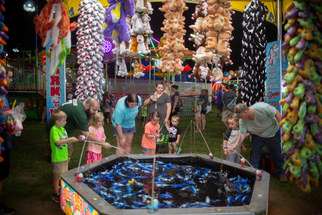 Visitors play a fishing game at the Maury County Fair and Exposition held at the Maury County Park in Columbia, Tenn., on Thursday, Sept. 3, 2020.