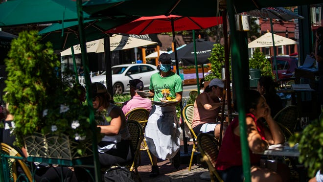 A waiter in a face mask delivers food to the tables outside of a local restaurant during lunch Friday in Hoboken, N.J.