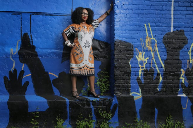 Color Jax Blue co-founder Shawana Brooks poses alongside an old commercial building on Myrtle Avenue being turned into a three-walled mural. The first phase of the project will feature the work of local Black artists with themes of voting, justice and women in activism.