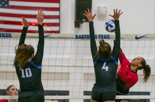 Creekside outside hitter Jaden McBride hits through the block of Bartram Trail's Lauren Marien (4) and Brooke Shiver (10) during a 2019 match.