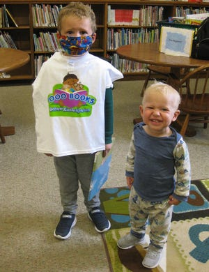"""Greyson Spry, left, shows off the t-shirt he earned for reaching the 1,000 book milestone in the Aurora Memorial Library's """"1,000 Books before Kindergarten"""" program. His brother, Ryder, right, has reached the 600-book milestone through the program that encourages parents to share the joys of reading with their young children. To register children or for more information on this program, contact the library at 330-562-6502."""