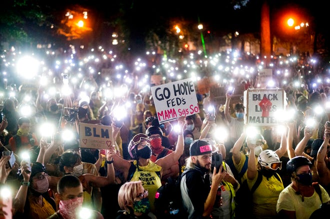 In this July 20, 2020, file photo, hundreds of Black Lives Matter protesters hold their phones aloft in Portland, Ore. Once hailed as one of the most livable cities in the U.S., Portland, Oregon, is grappling with an uncertain future as it reaches a stunning benchmark: 100 consecutive nights of racial injustice protest.