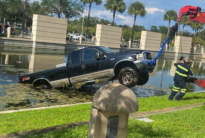 In this photo provided by the Florida Highway Patrol a vehicle is removed from a pond after it crashed  outside the Pinellas County Justice Center Wednesday in Clearwater. The 64-year-old driver was attempting to pull into a spot when his boot became entangled with the accelerator and vaulted into the retention pond, according to the Florida Highway Patrol. The truck became fully submerged, but deputies at the courthouse were able to help the man to safety.