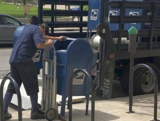 A U.S. Postal Service worker removes a mailbox from a sidewalk in Columbus, Ohio, on Sept. 1. The Postal Service would not confirm if similar actions involving sorting machines or collection boxes had occurred in Polk County. BETHANY BRUNER/COLUMBUS DISPATCH