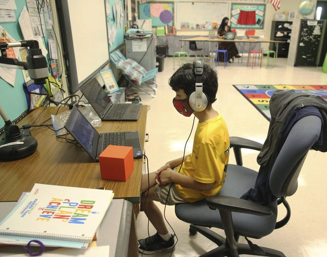 Nova Blanche Forman Elementary School teacher Attiya Batool teaches her fourth-grade class virtually as her son, Nabeel, does his second grade classwork online wearing a face mask and headphones during the first day of school in in Davie in August. .  (Emily Michot/Miami Herald via AP, File)