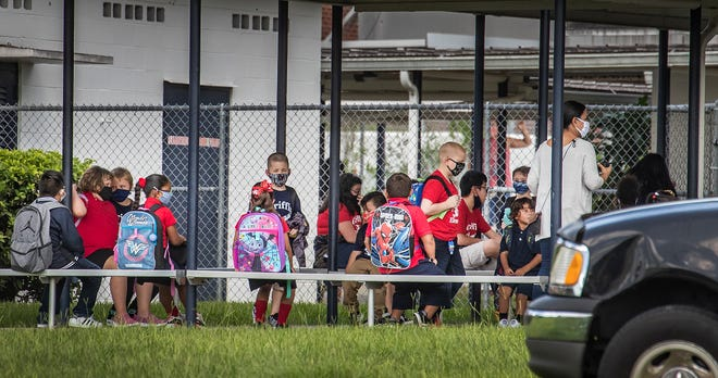 Griffin Elementary students wait in the car line to be picked up at the end of the school day on Thursday in Lakeland. ERNST PETERS/THE LEDGER