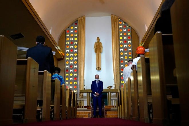 Then-candidate Joe Biden bows his head in prayer at Grace Lutheran Church in Kenosha, Wis.