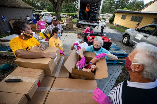 Volunteers sort through items delivered by a truck from Feeding Tampa Bay on a recent Thursday morning at the Unitarian Universalist Congregation of Lakeland. It Takes a Village Coalition operates the drive-up food pantry and also deliver to 160 families.
