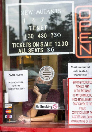 Jewel Stacey sits at the ticket booth waiting for customers Friday afternoon at the Belleview Cinema in Belleview. Employees were pulling down old movie posters from almost six months ago when the COVID-19 pandemic forced theaters to close.