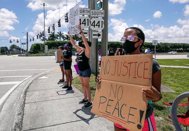 Wellington resident Maya Rose takes part in a peaceful Black Lives Matter rally at the intersection of 441 and Forest Hill Boulevard in June. [DAMON HIGGINS/palmbeachpost.com]