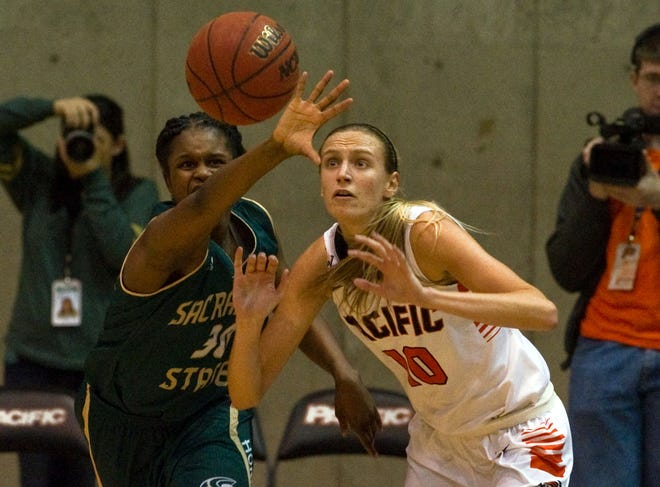 Pacific's Kendall Kenyon and Sac State's Kyhonta Doughty fight for a loose ball in an opening round game of the Women's National Invitational Tournament at University of the Pacific's Spanos Center in Stockton.[CLIFFORD OTO/STOCKTON RECORD FILES]