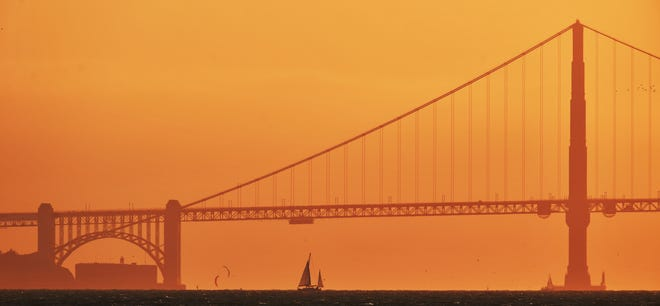 A sailboat sails past the Golden Gate Bridge as viewed from Treasure Island in San Francisco. Triple-digit temperatures are likely over a vast stretch of the state, and even coastal areas could see higher temperatures, forecasters said.