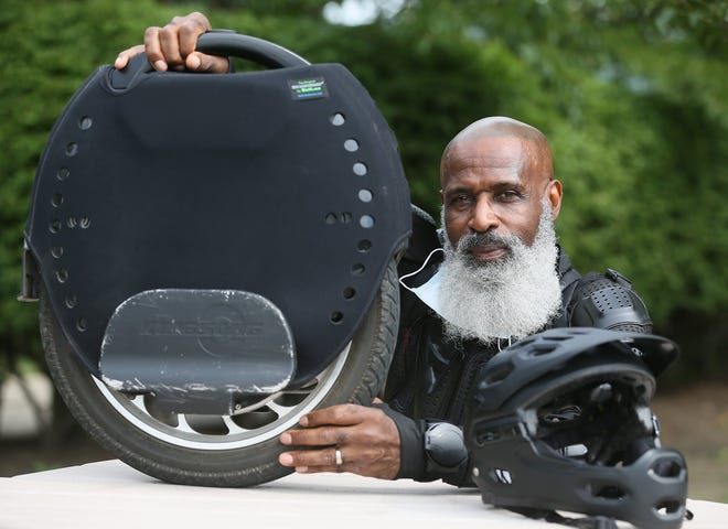 Tony Roberson, 68, of Twinsburg shows his electric unicycle in Akron on Thursday Sept. 3, 2020.   Roberson zooms all over NE Ohio on the device which can hit speeds up to 31 mph.   [Mike Cardew/Beacon Journal]