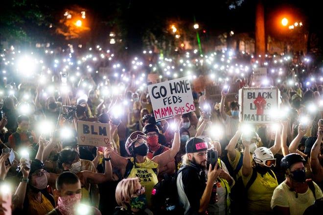 Hundreds of Black Lives Matter protesters hold their phones aloft in Portland, July 20.
