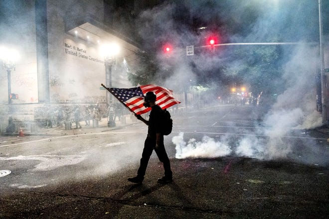 A Black Lives Matter protester carries an American flag as teargas fills the air outside the Mark O. Hatfield United States Courthouse in Portland, July 21.