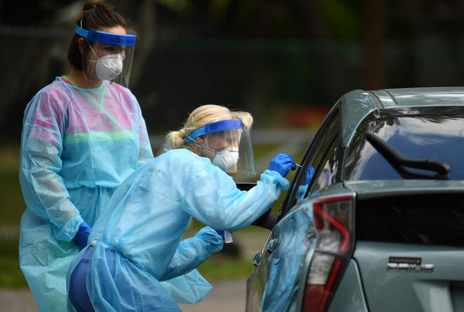 Nurses Katelyn Escanillas, left, and Beth Banko, right, collect samples from drivers for the Department of Health Sarasota's COVID-19 testing efforts in this archive photo from May.