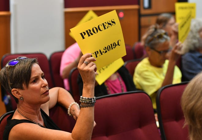 Wendy Rossiter and others hold up protest signs at a meeting where Sarasota County commissioners were considering a citizen-initiated comprehensive plan amendment to curtail development in the northeast corner of the county.
