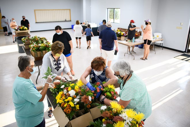 From left, Carrie Bell, Jan Jernigan, Phyllis Turnage and Caroline Elmore work on arranging flowers in vases at the Dunn Community Center on Friday. The flowers are for a community project known as 'Project Not Forgotten' and will be delivered to nursing homes in Dunn, Erwin, Coats, Angier, Lillington, Fayetteville, Clinton and other surrounding towns for the patients and staff in each nursing home.