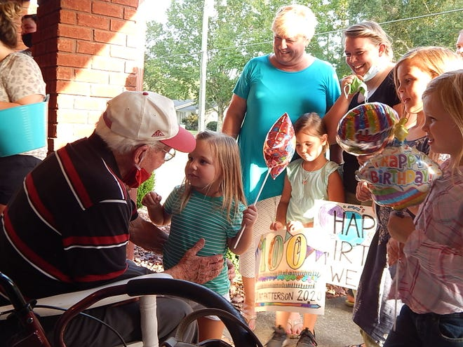R.B. Patterson greets a young friend during his drive-by birthday celebration. Patterson turned 100 Wednedsay.