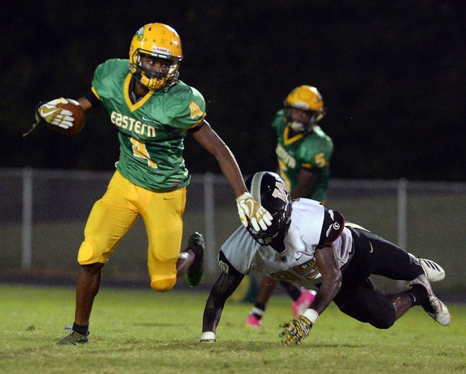 Eastern Alamance's Darius Kane carries the ball for a first down pushing away Williams defensive end Imanuel Ellis.