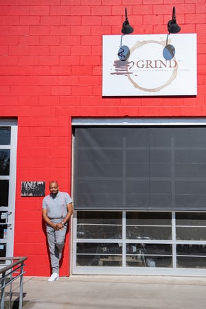 J. Hackett stands outside Grind Coffee Co., the coffee shop he owns with business partner Gene Ettison.