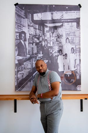 J. Hackett stands with an historic photograph of a black-owned Asheville business, one of several prominently displayed on the walls of the coffee shop he opened with business partner, Gene Ettison, in the River Arts District.
